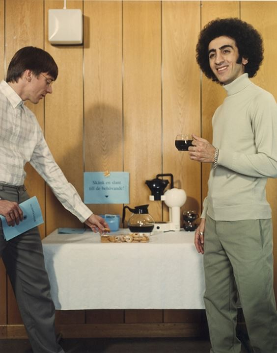 Two young men standing near a table