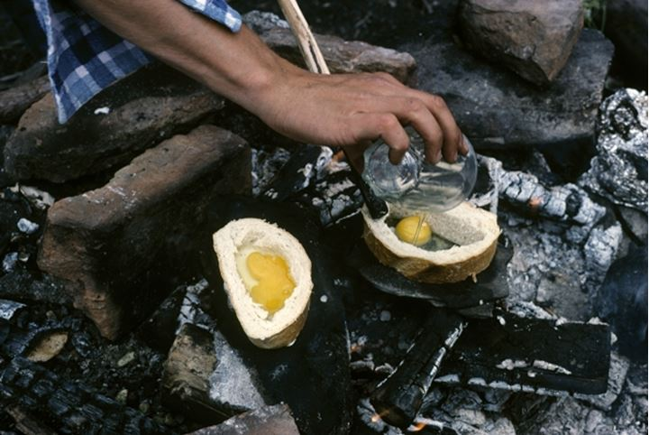 Man frying eggs on hot stones