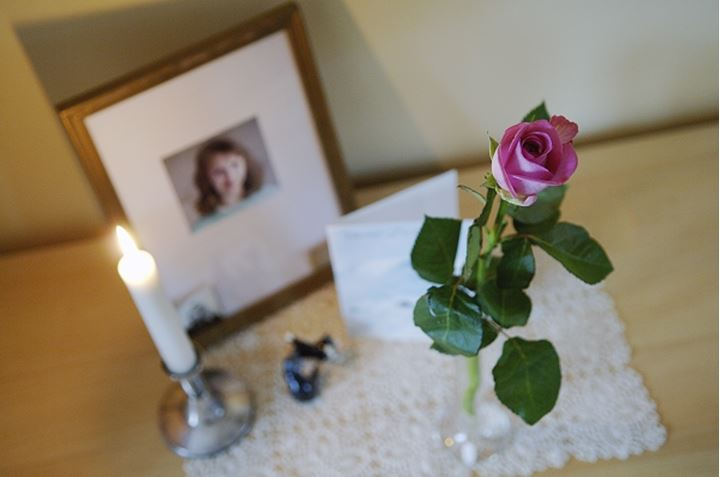 Overhead view of rose flower with lit up candle and photo frame