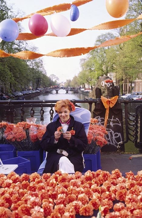 Front view of a woman sitting by flowers during queen's birthday on 30th April in Amsterdam, Holland