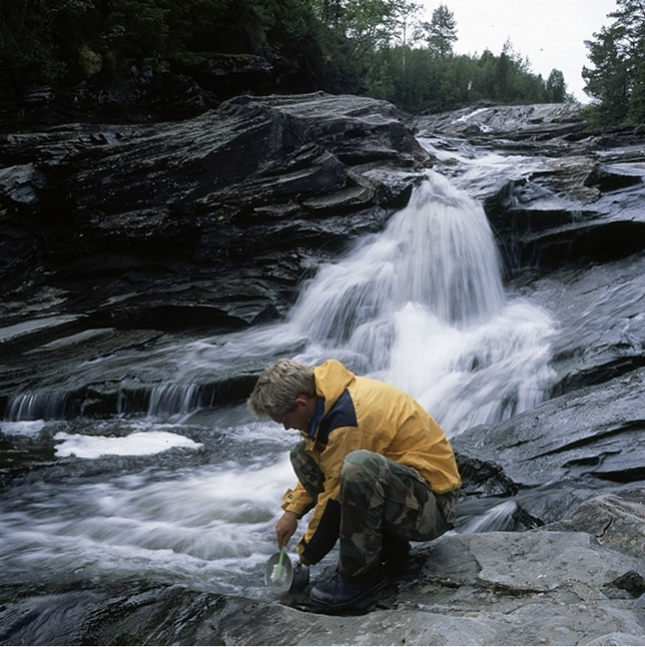 Side view of a man washing pot by waterfall