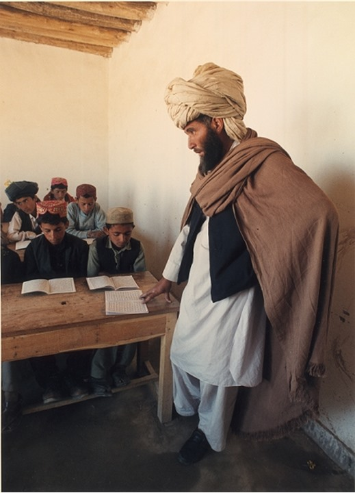 A male teacher standing in the classroom with students in Afghanistan