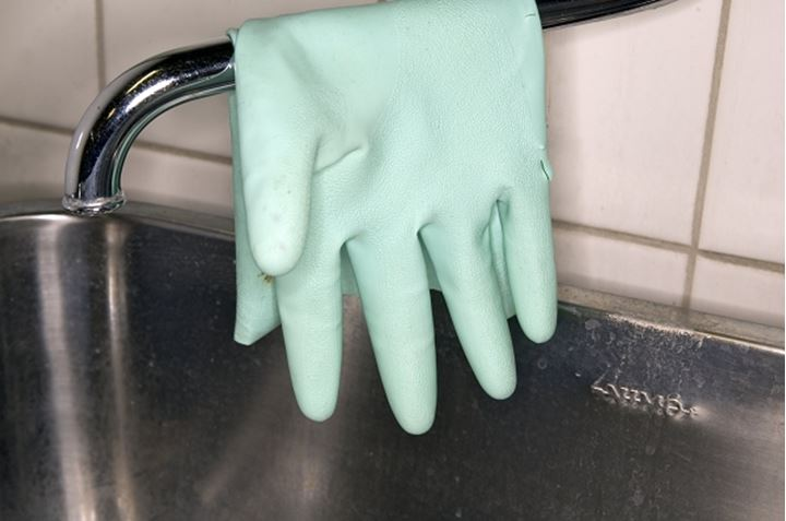 A plastic glove hanging in the kitchensink