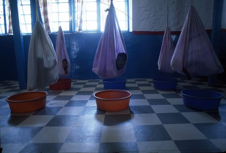 Young children in cotton hammocks; the buckets are there for when when they pee (urinate), creche, India