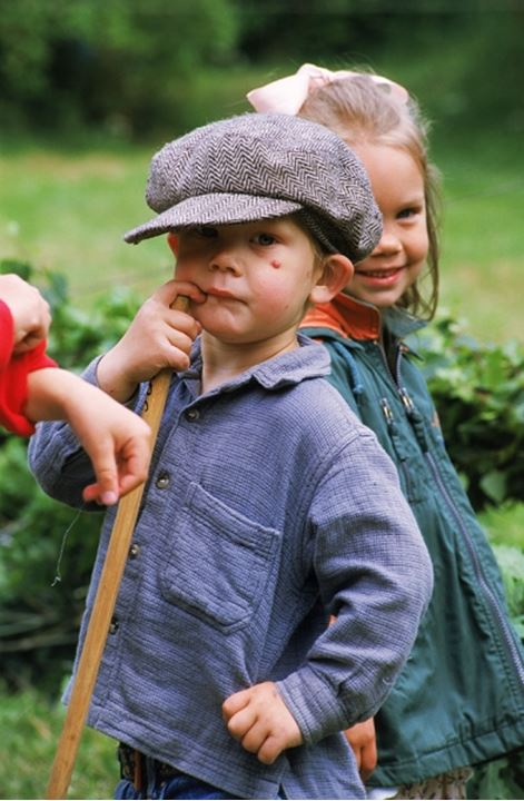 Boy with hat playing with mates outdoors