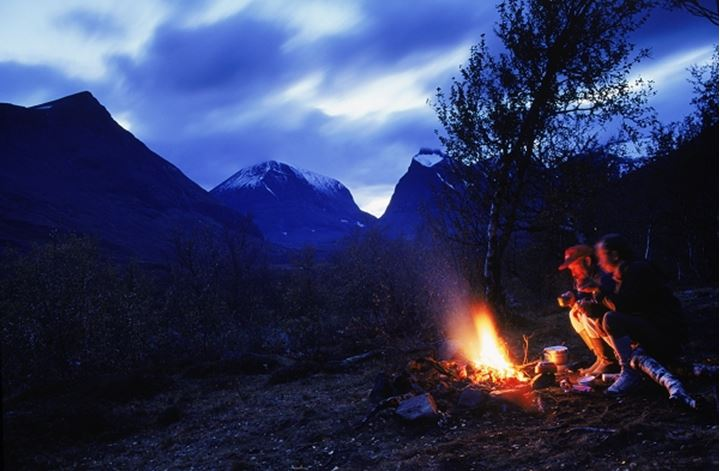 Two hikers at campfire in Swedish Arctic wilderness called Sarek National Park