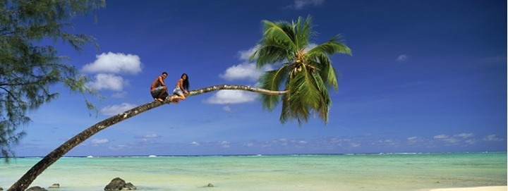 Young Polynesians on trunk of palm tree over Aitutaki beach in Cook Islands
