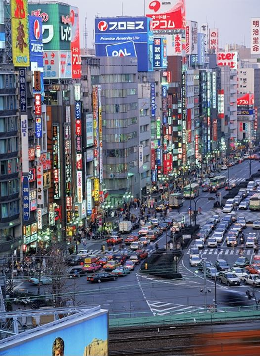 Traffic, stores and office buildings in Shijuku District at dusk in Tokyo