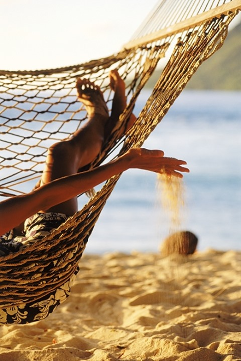 A woman playing with sand and lying in the hammock, Huahine Island, French Polynesia.