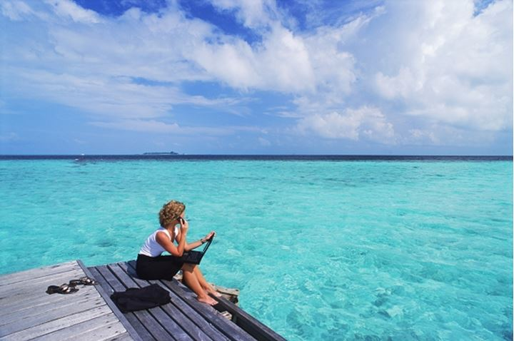 Woman with laptop and cellphone on working holiday in Maldives