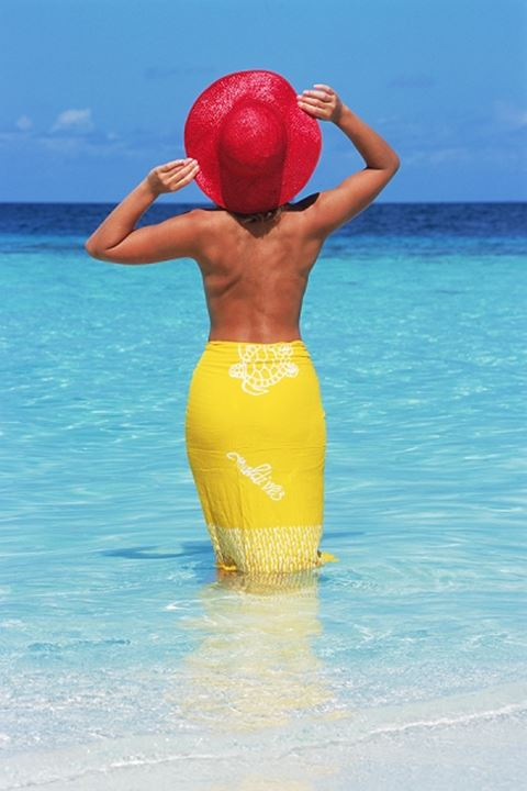 Back view of topless woman with red hat and yellow pareo in shallow water