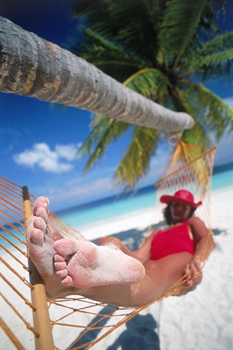 Woman in red hat and bathing suit sleeping in hammock with sandy feet