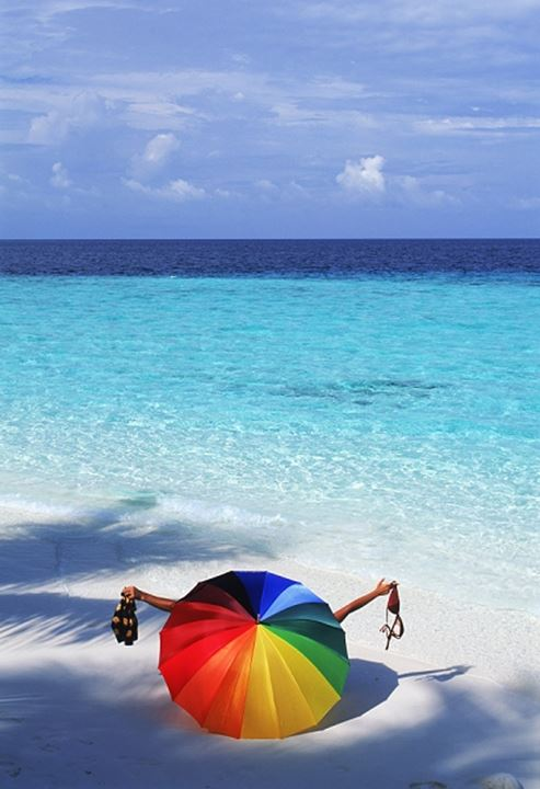 Couple undressing behind colorful parasol on sandy shore in Maldives