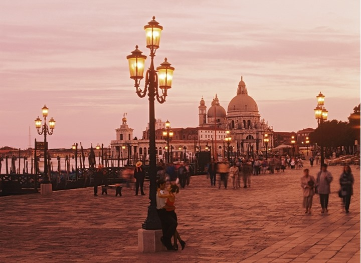 Couple embracing against lamp post on waterfront walkway near Piazza San Marco or St. Marks Square in Venice at sunset