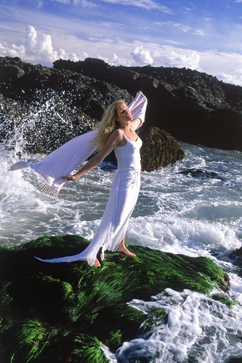 Woman in white dress on wave swept rocky shore in California