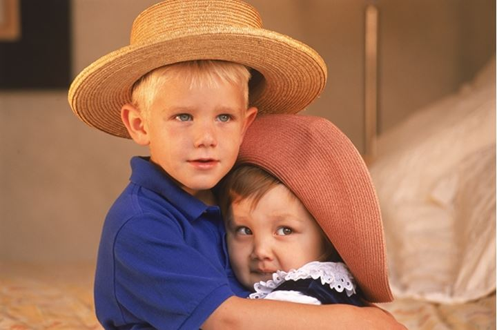 Boy and girl 3 to 5 years old hugging with hats on at home