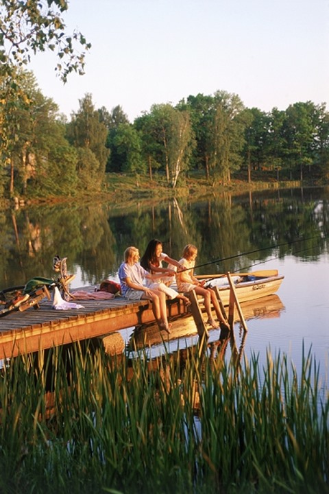 Three females on fishing picnic on lakeside pier in Sweden at sunset