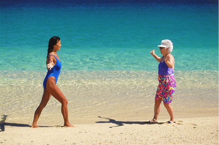 80 year old grandmother and 40 year old mother doing yoga and Tai Chi exercises on beach