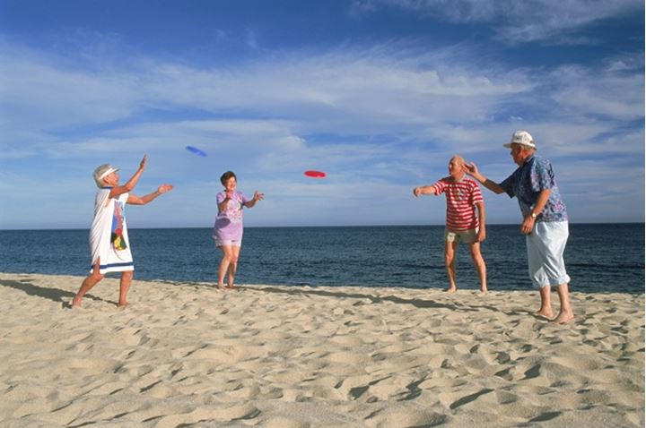 Four seniors tossing frisbees on beach at Cabo San Lucas Mexico