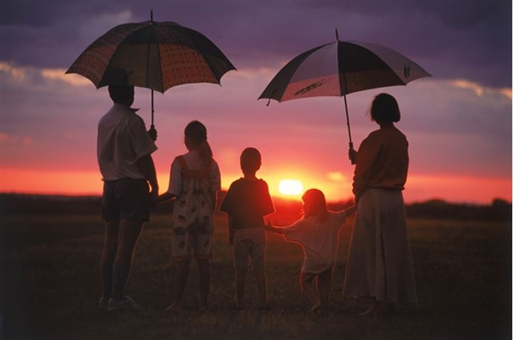 Family of five watching African sunset under rainy skies in Zimbabwe