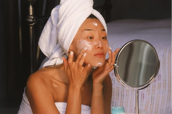Asian woman after bath applying facial cream with small mirror