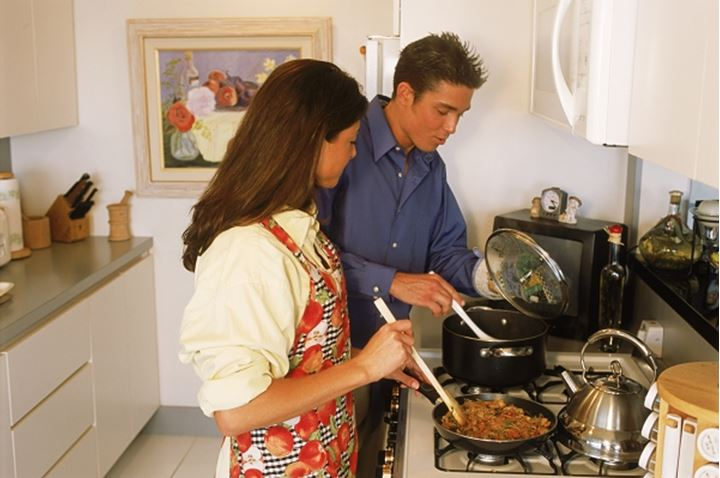 Couple in their twenties in kitchen cooking together