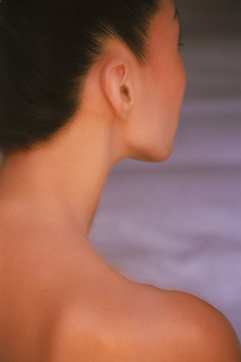 Profile of Asian womans face neck and shoulder looking away