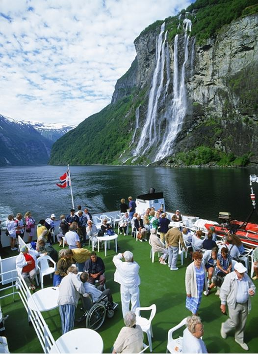 Passengers on deck of car ferry on Geirangerfjord in Norway