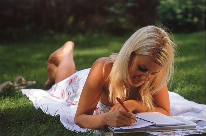 Young blond lady reading and writing outside in summer dress