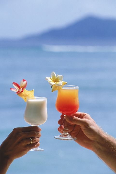 Couple on island holiday toasting with tropical drinks