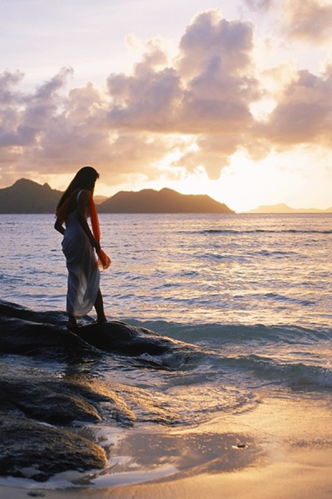 Woman in long white dress alone at sunset on La Digue Island