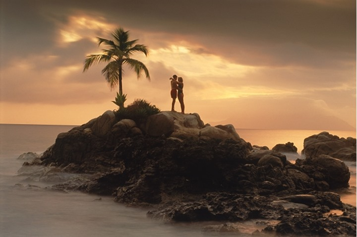 Couple on rocky point with one palm tree off Mahe Island in Seychelles at sunset