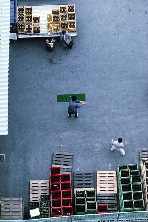 Japanese worker practicing golf swing in parking lot of beer bottling company in Tokyo