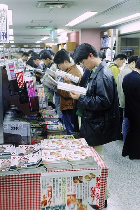 Young Japanese people filling aisles reading magazines in Tokyo bookstore