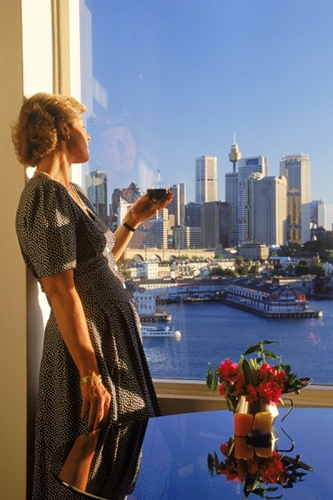 Woman in North Sydney apartment on Sydney Harbour with afternoon glass of wine