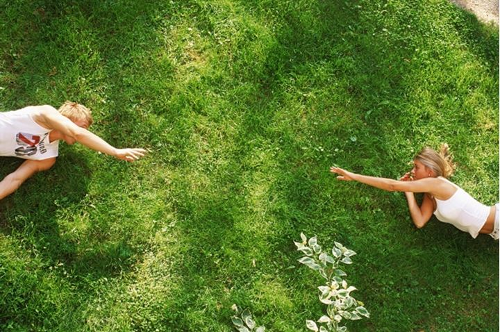 Young man and woman reaching for eachother across sunlit green grass, Sweden.