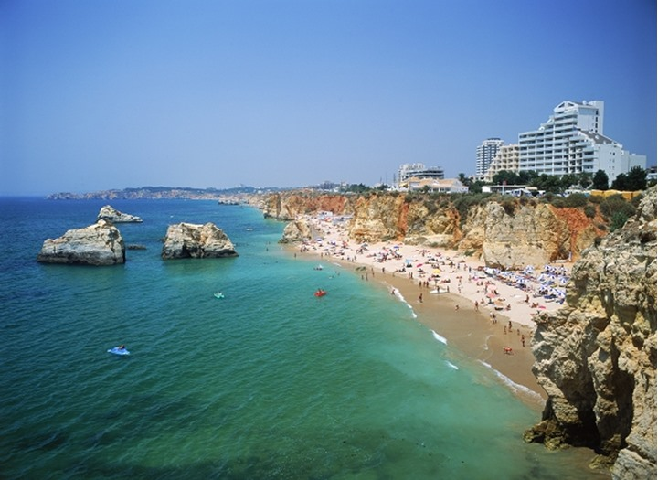Hotels and sunbathers on Mediterranean beaches along Praia da Rocha in Portugal