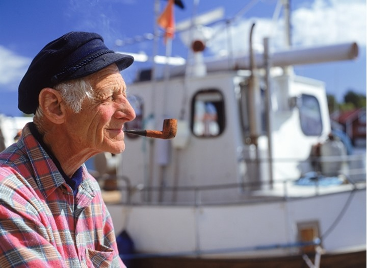 Profile of elderly fisherman with pipe and fishing boat at Kuggoren in Baltic Sea off Sweden's East Coast