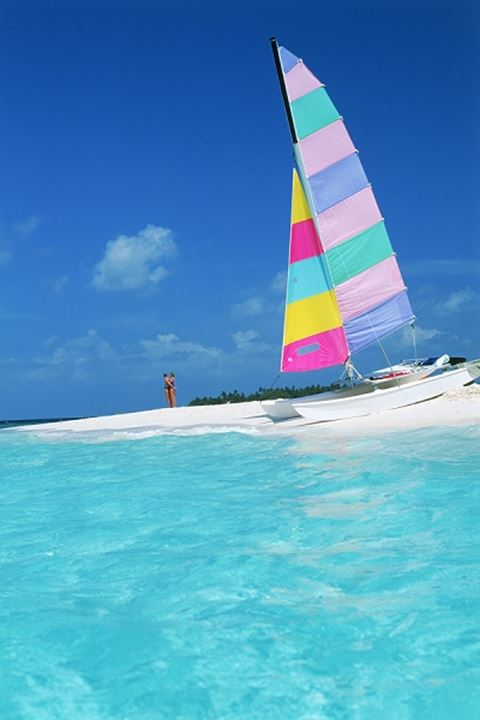 Couple with their catamaran parked on sandy shore in Maldive Islands