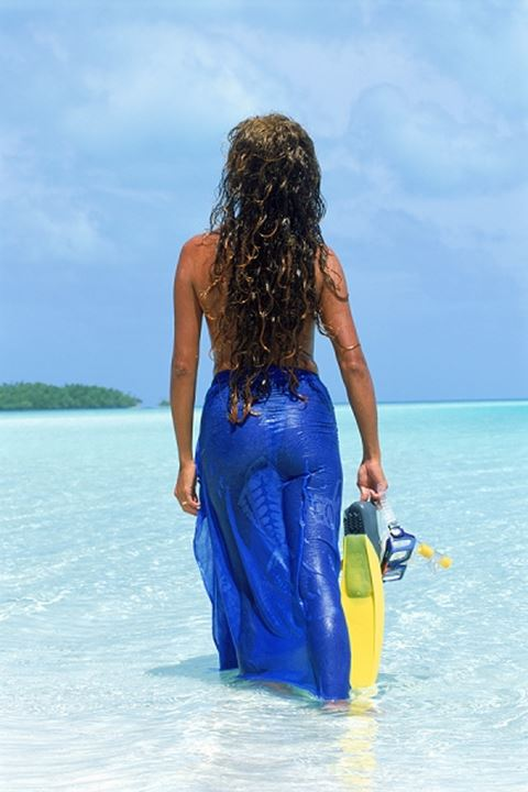 Woman with long wet auburn hair and swim fins in blue pareo in shallow waters of Cook Islands