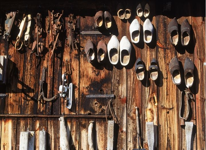 Wooden shoes, skates and farming tools hanging on old barn wall in Sweden