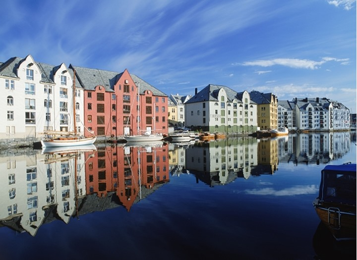 Houses and boats along canal at sunrise in Alesund, Norway