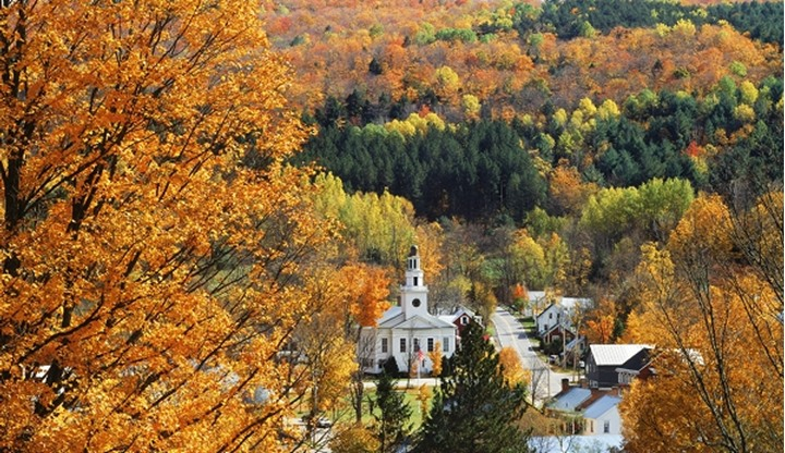 Fall foliage surrounding village church at Chelsea in Vermont USA
