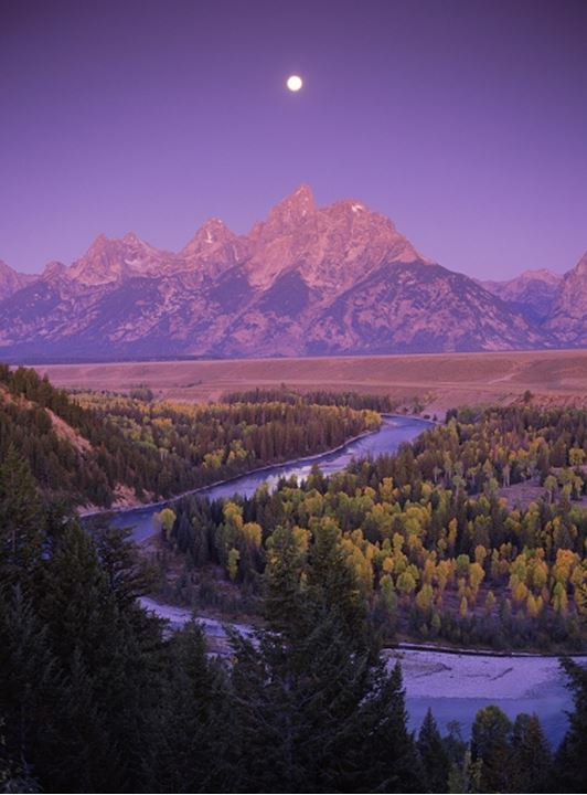Moon over Mount Moran in Grand Tetons above Snake River at dawn near Jackson, Wyoming