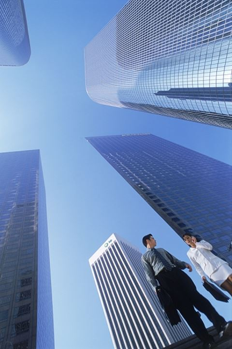 Businessman and woman under downtown Los Angeles skyscrapers