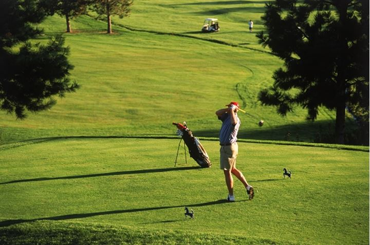 Male golfer teeing off in low light at Sunset Ranch Golf Club in Kelowna, British Columbia Canada