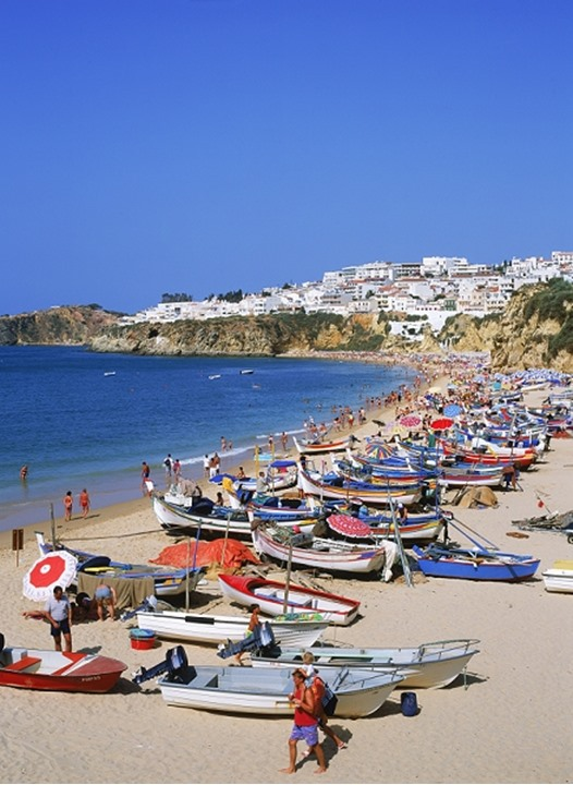 Colorful fishing boats and tourists on Albufeira beach in Algarve, Portugal