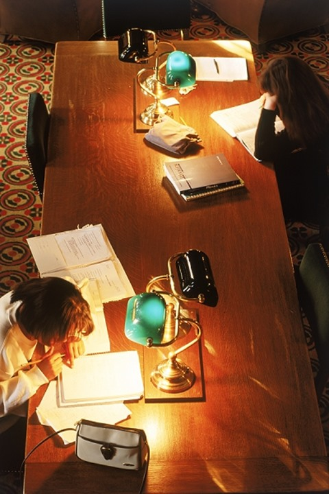Two students in school library with workbooks and pens under lamplight