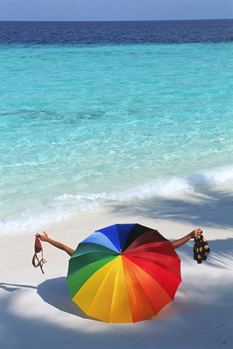 Couple on white sandy beach undressing behind large colorful parasol