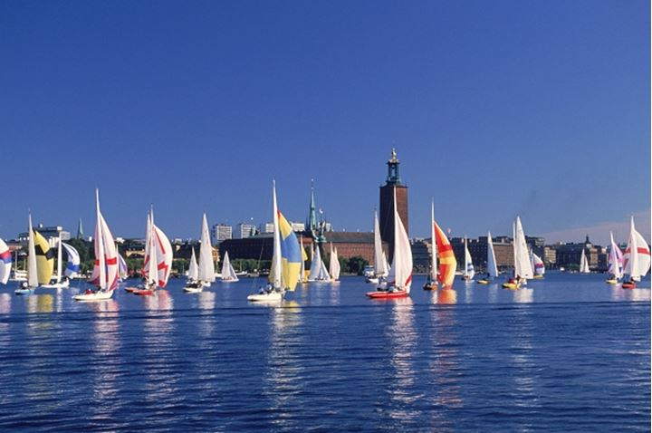 Colorful spinnakers on Riddarholmen waters during summer regatta in Stockholm with Town Hall beyond
